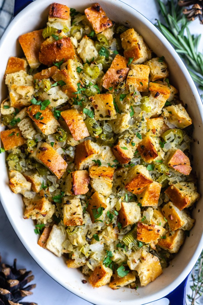 casserole dish filled with a simple vegan stuffing recipe topped with fresh herbs