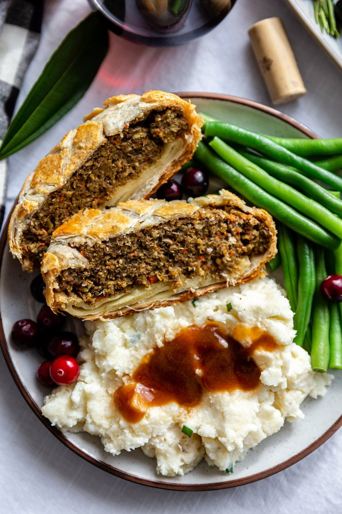 2 slices of vegetarian wellington on a plate with mashed potatoes and gravy, fresh green beans, and fresh cranberries