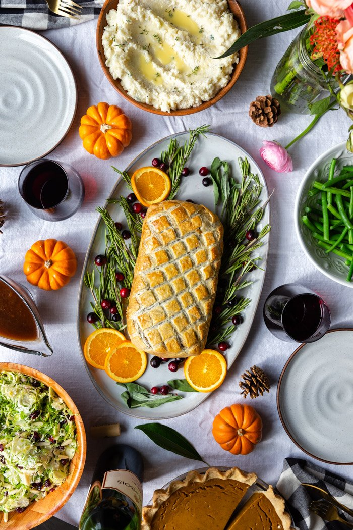 tablescape with a vegetarian wellington on a large platter surrounded by herbs and fresh fruit. Bowl of mashed potatoes and flowers on the side as well as bowls of green beans and salad