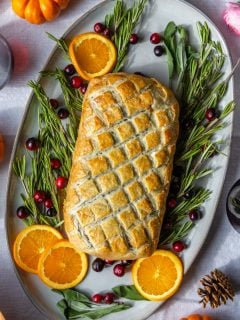 vegetarian wellington on a large platter surrounded by rosemary, orange, and fresh cranberries