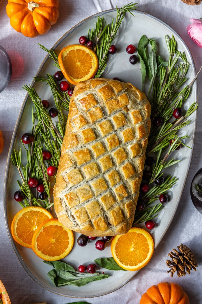 vegan wellington on a large platter with herbs and fresh fruit around it