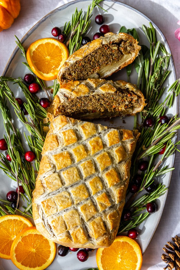 vegetarian wellington on a large platter surrounded by rosemary, orange, and fresh cranberries. several slices have been cut out of the wellington
