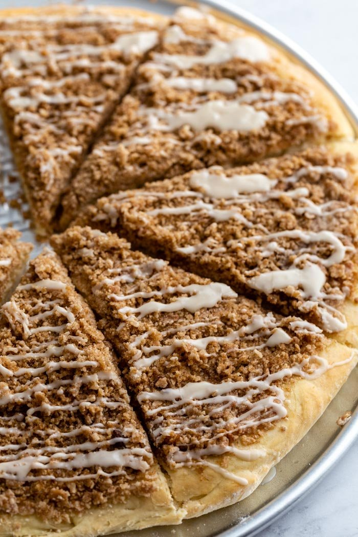 cinnamon sugar dessert pizza cut in slices and topped with a frosting.