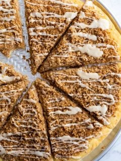 cinnamon sugar dessert pizza cut in slices and topped with a frosting. a bite is taken out of one slice