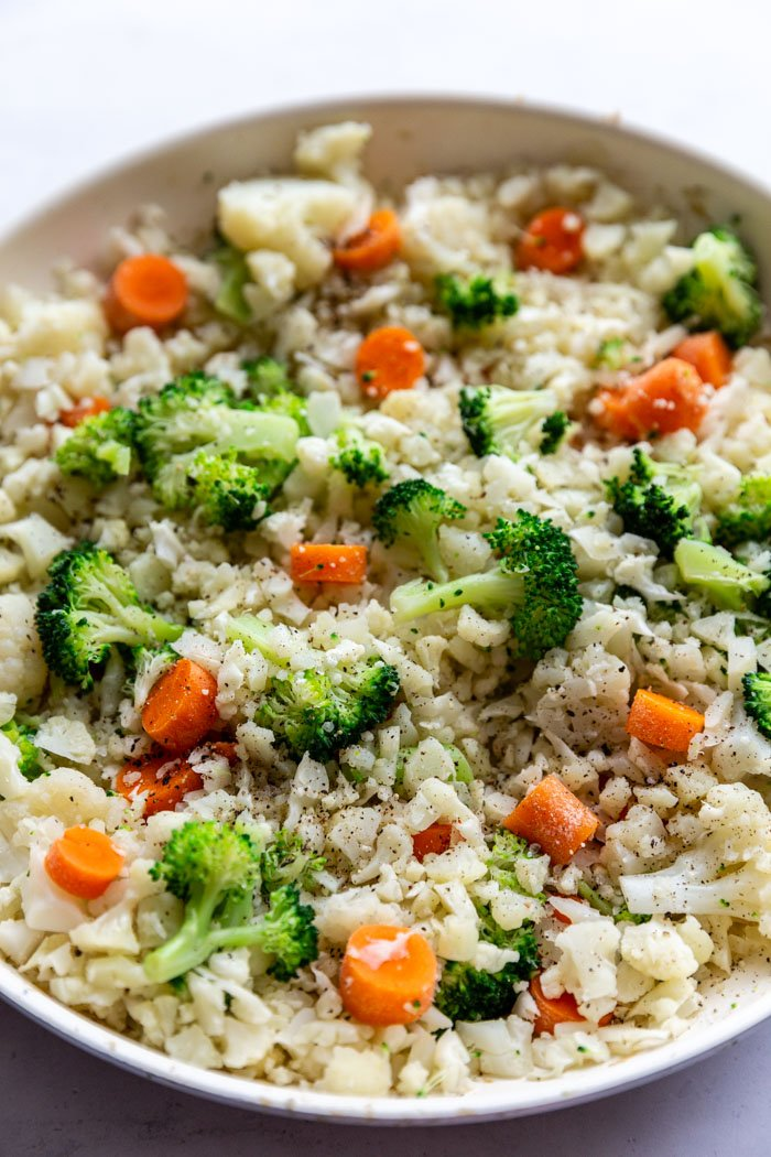 skillet with cauliflower fried rice that has broccoli and carrots in it