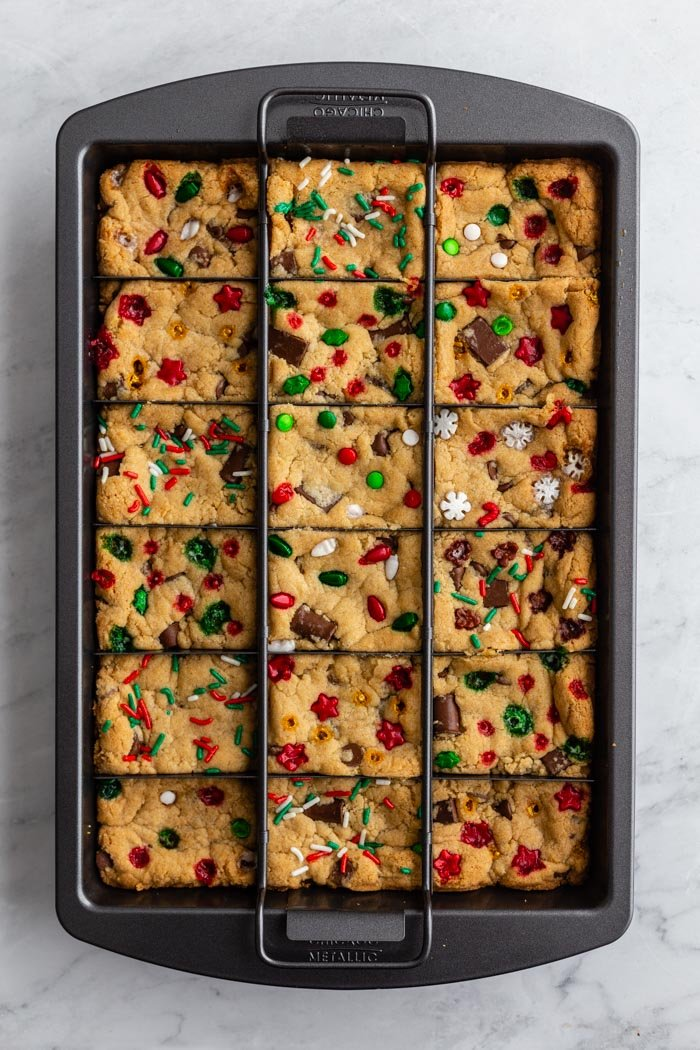 chocolate chip cookie bars in a slice solution pan with christmas sprinkles on top