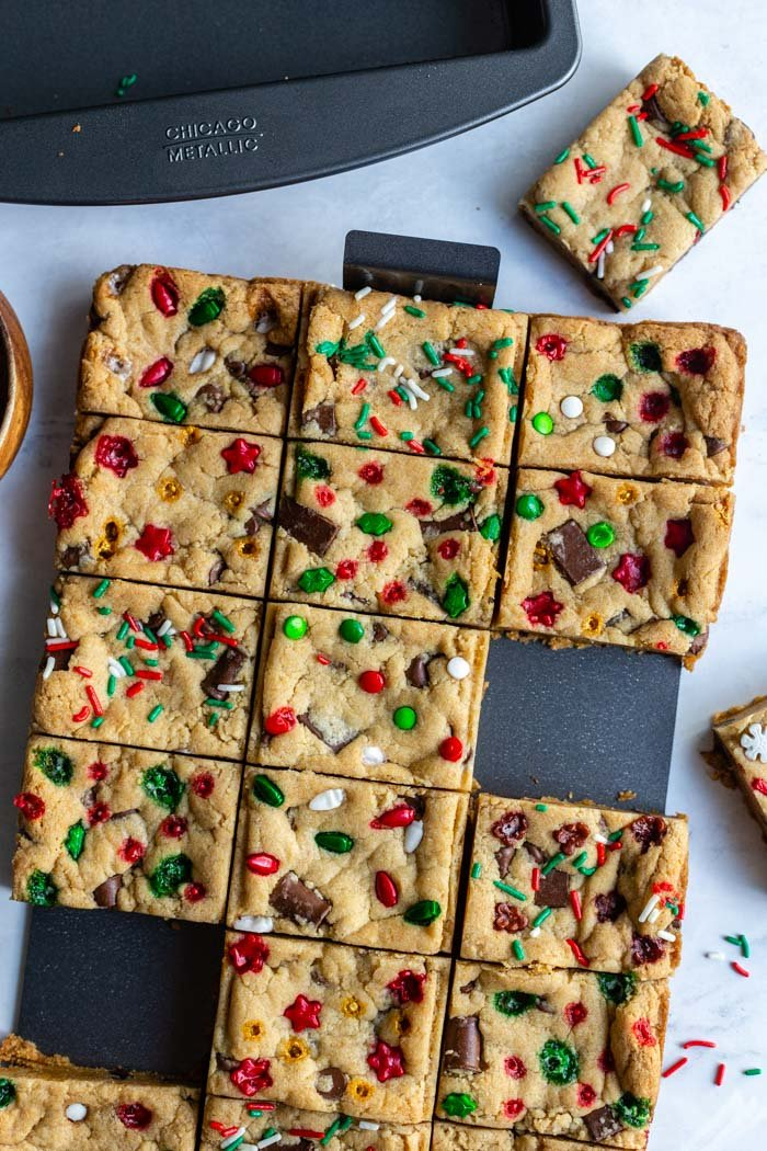 chocolate chip cookie bars in a slice solution pan with christmas sprinkles on top. several bars are taken off of the tray