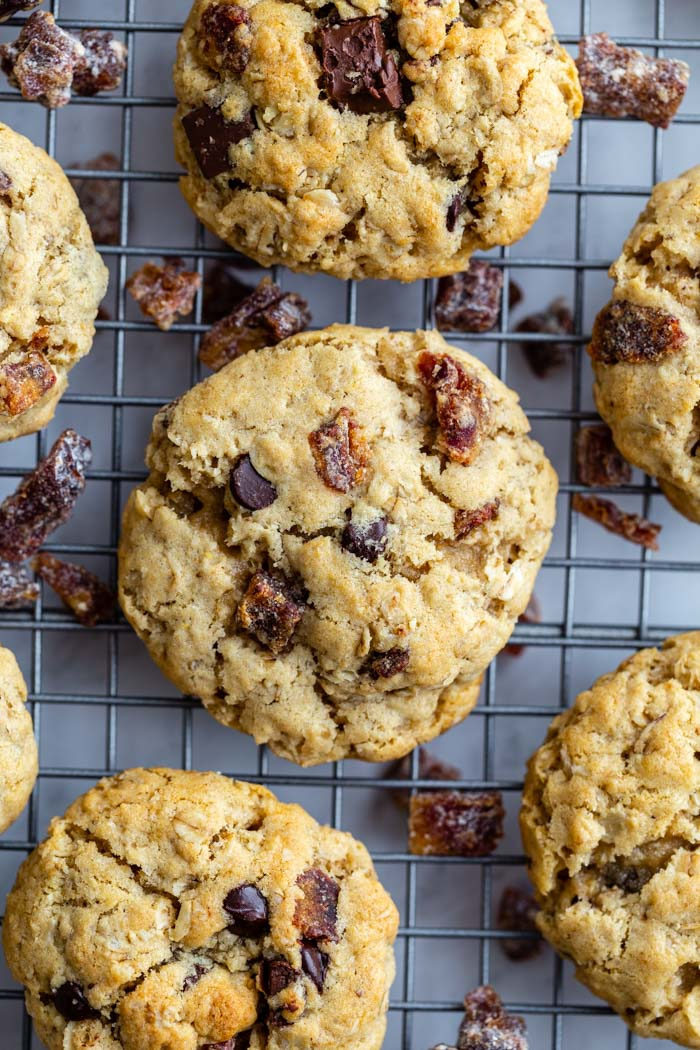 chocolate chunk date cookies on a cooling rack with chopped dates around the cookies
