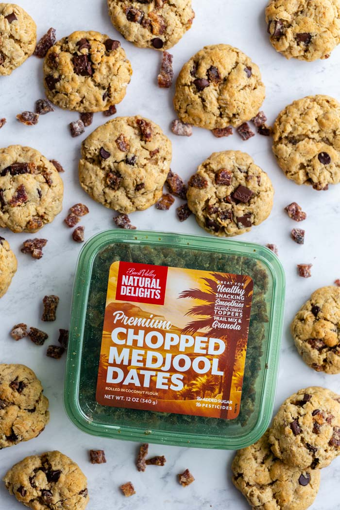 date oatmeal cookies on a table spread on with a package of natural delights chopped medjool dates in the corner