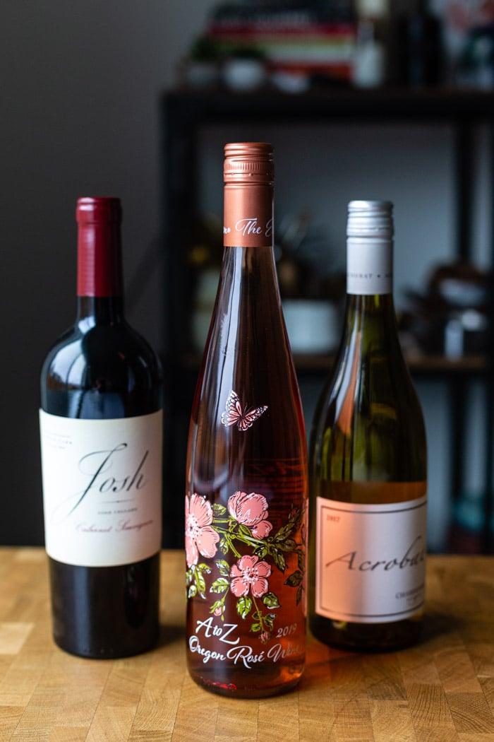 3 garrafas de vinho em uma mesa de madeira