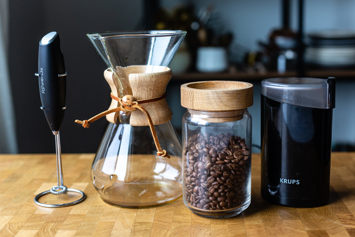 coffee making supplies on a table: whisk, chemex, coffee beans in a jar, and coffee grinder