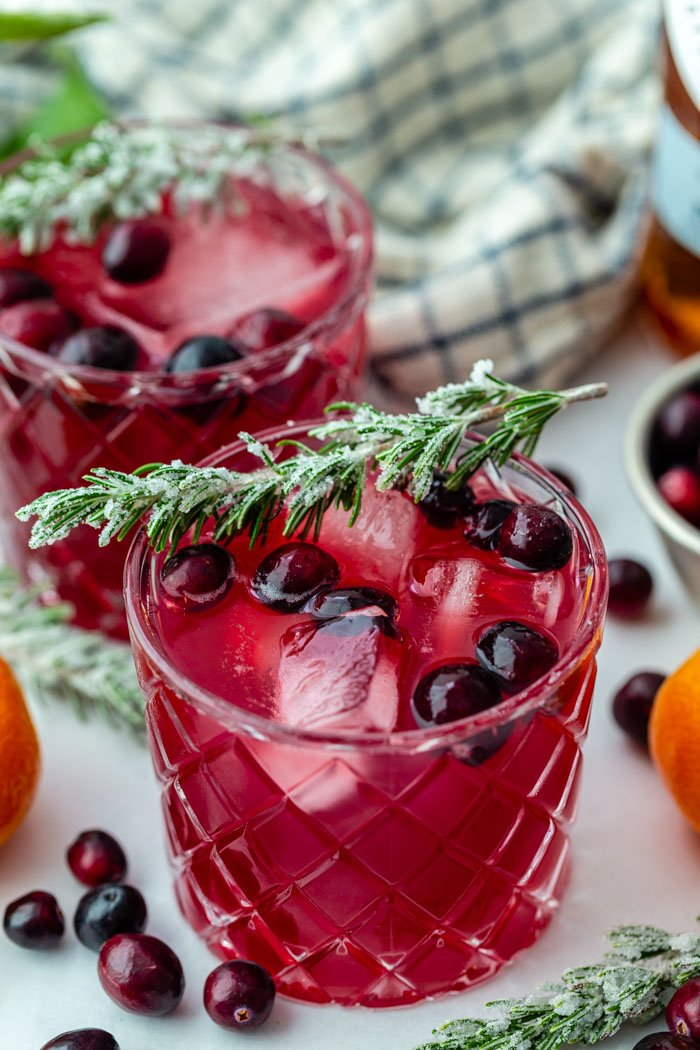 2 whiskey glasses filled with cranberry cocktail and fresh cranberries. topped with sugared rosemary