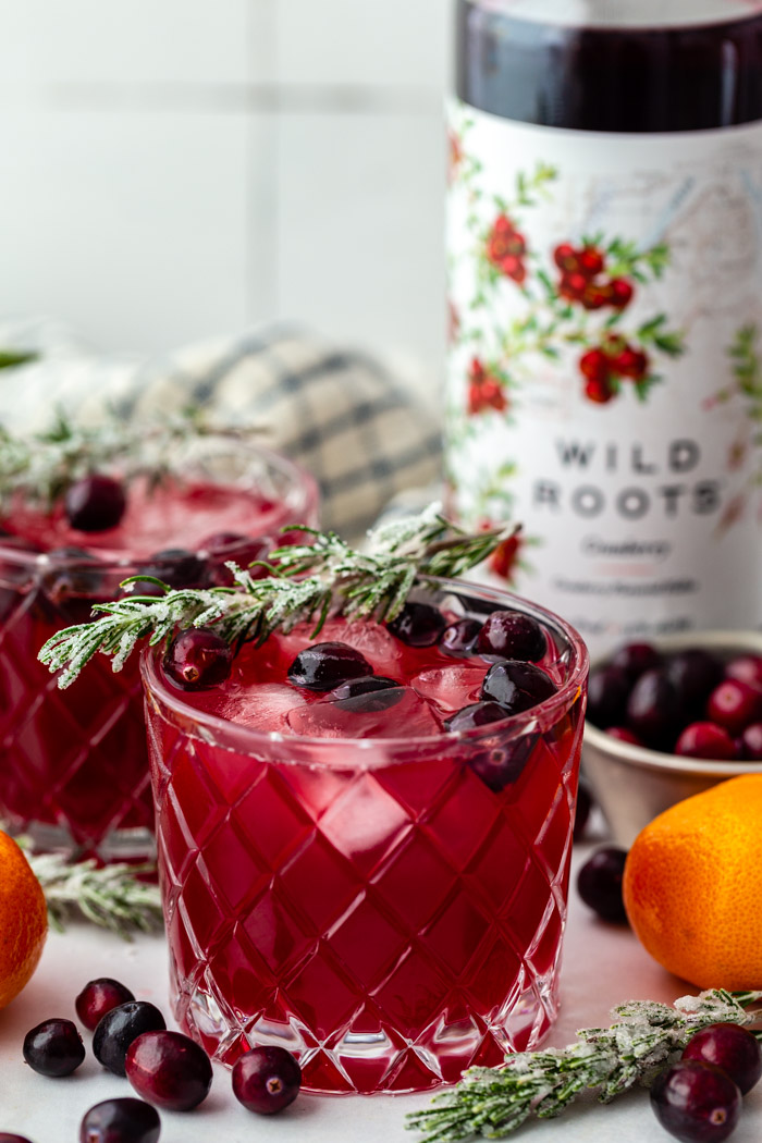 cranberry cocktail with rosemary on top and a bottle of cranberry vodka in the background