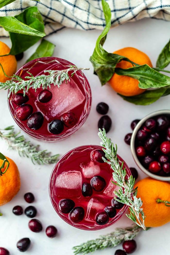 dose de cima para baixo de um coquetel de uísque de cranberry com cranberries frescas e alecrim açucarado na borda