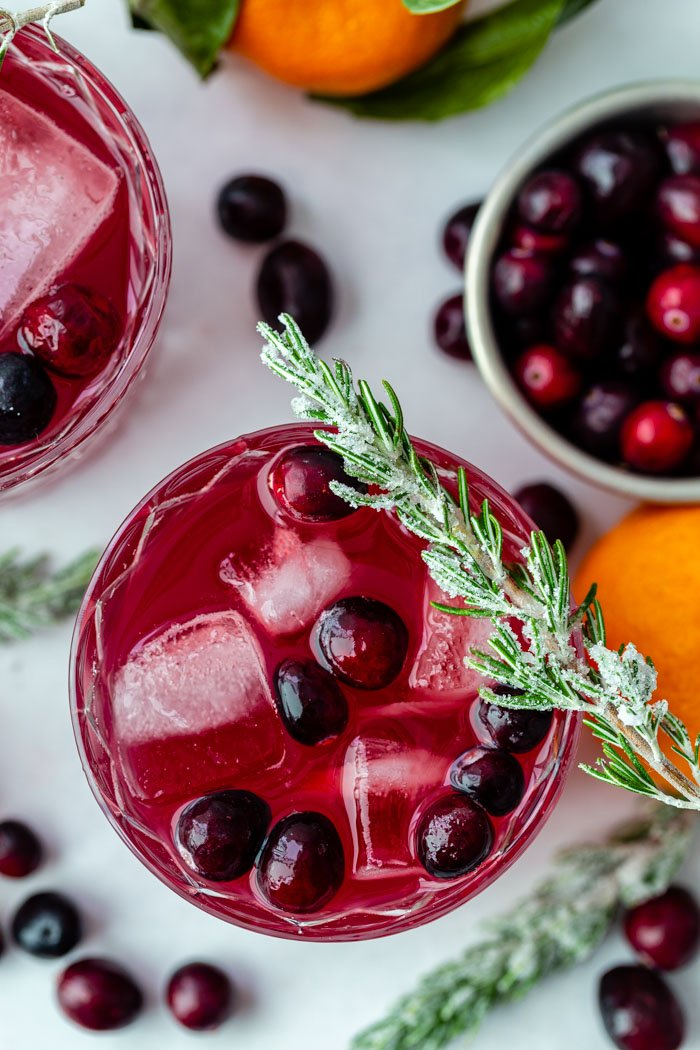 top down shot of a cranberry whiskey cocktail with fresh cranberries in it and sugared rosemary sitting on the rim