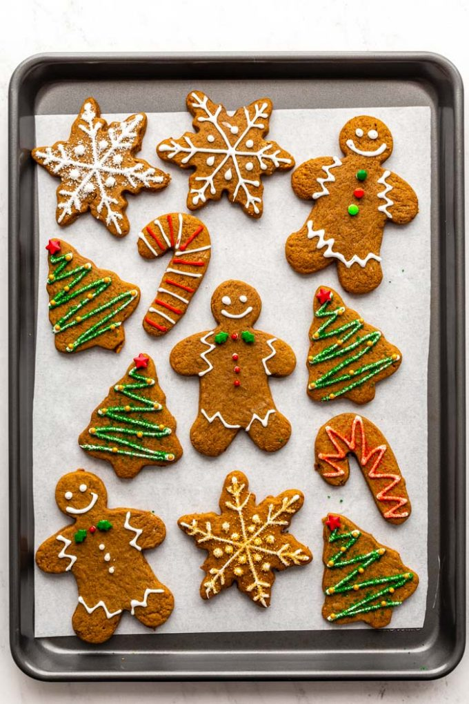 gingerbread cookies decorated with icing and sprinkles on a baking sheet