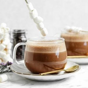 vegan hot chocolate in a clear glass with a stick of marshmallows on top of them. more hot chocolate in the background