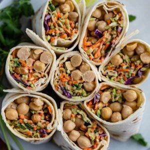 tortilla wraps filled with coleslaw mix and chickpeas. the wraps are cut in half and standing up on a plate so that you can see everything inside of them
