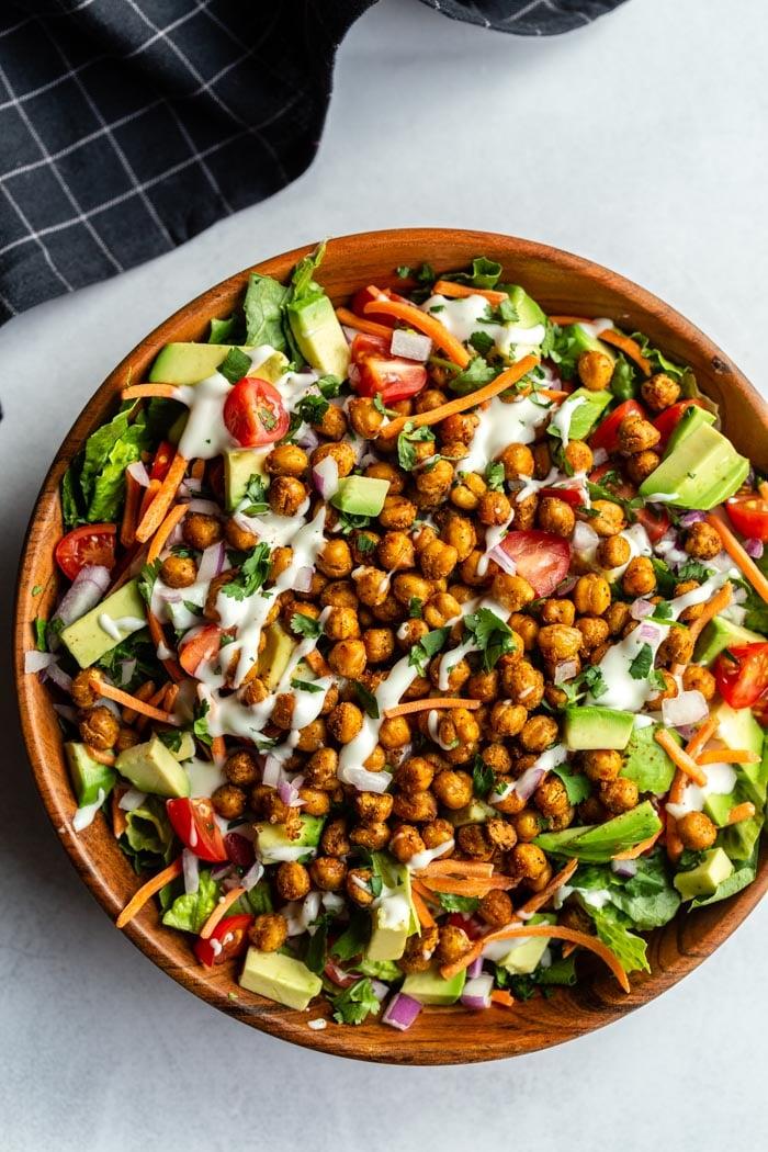 Salada grande em uma tigela de madeira com alface e vegetais picados, coberta com grão de bico assado e regada com molho de rancho vegan