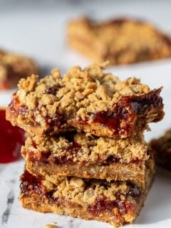 peanut butter and jelly crumble bars stacked on top of each other with more in the background