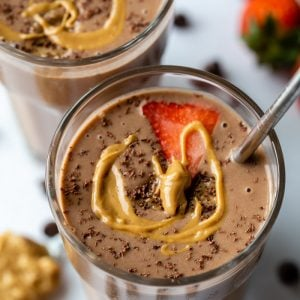2 glasses filled with a chocolate peanut butter smoothie and topped with a slice of strawberry, shredded chocolate and a drizzle of peanut butter