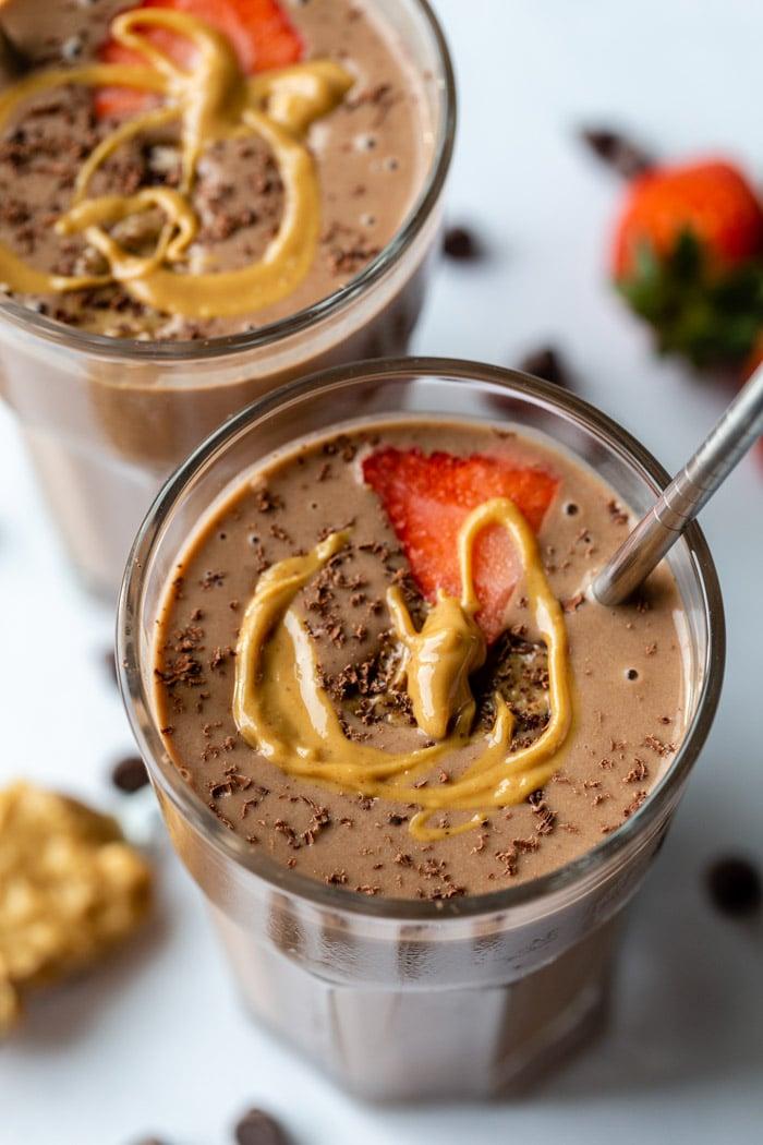 2 copos cheios de um smoothie de manteiga de amendoim de chocolate e coberto com uma fatia de morango, chocolate ralado e um fiozinho de manteiga de amendoim
