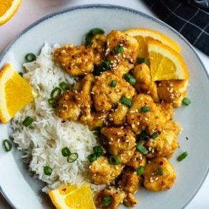 orange tofu served over rice with orange wedges