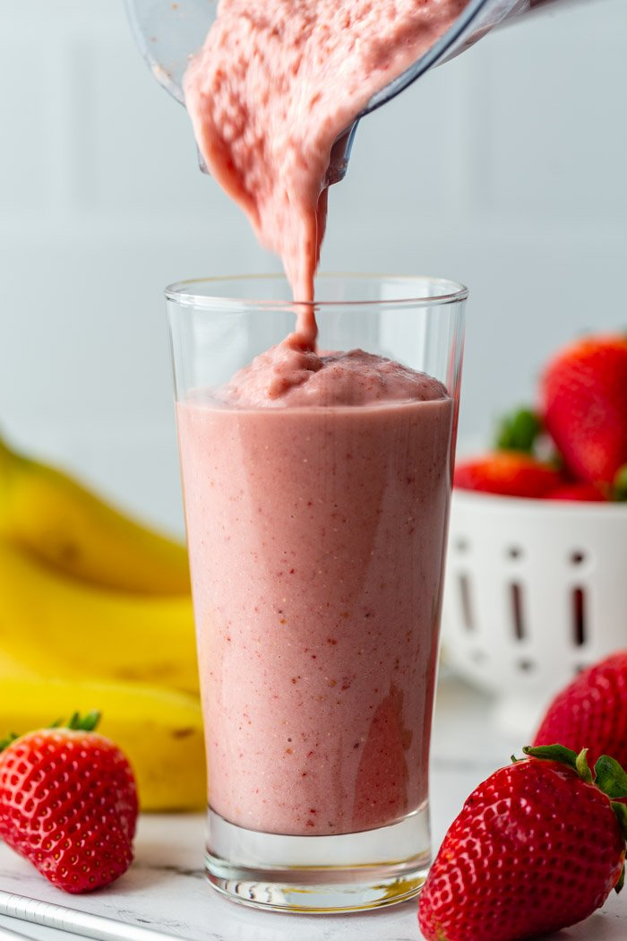 tall glass filled with a bright pink strawberry banana smoothie with fresh strawberries and bananas in the background