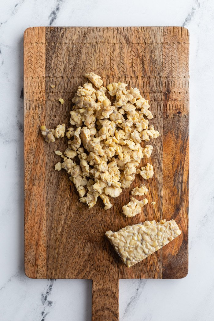 crumbled tempeh lying on a wood cutting board