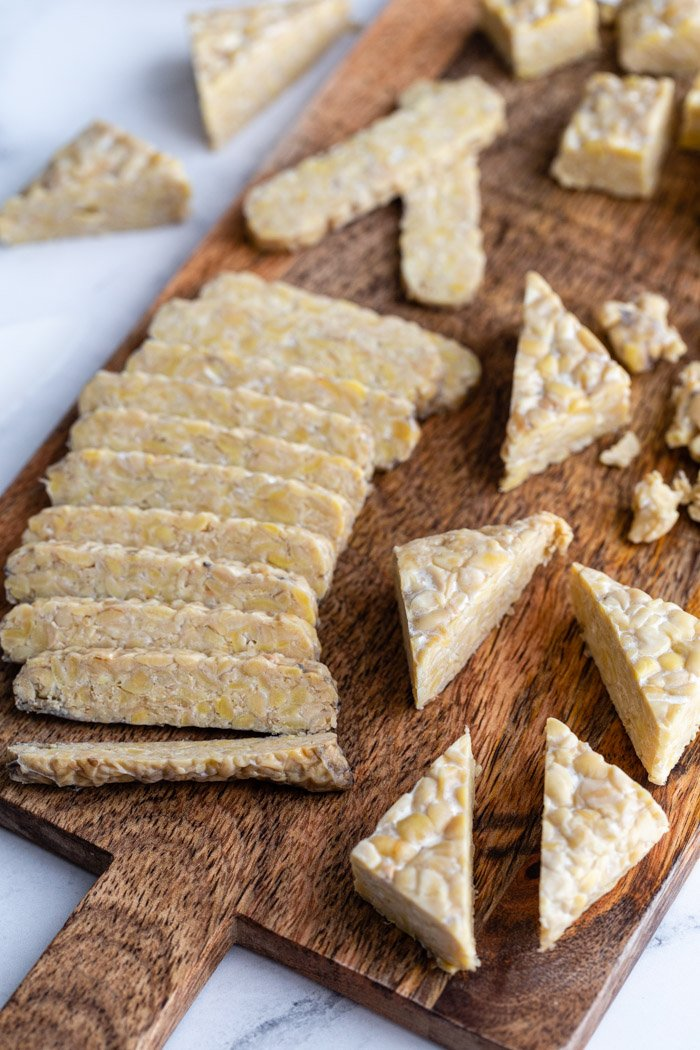 tempeh on a wood cutting board cut in several different ways including slices, cubed, and triangles