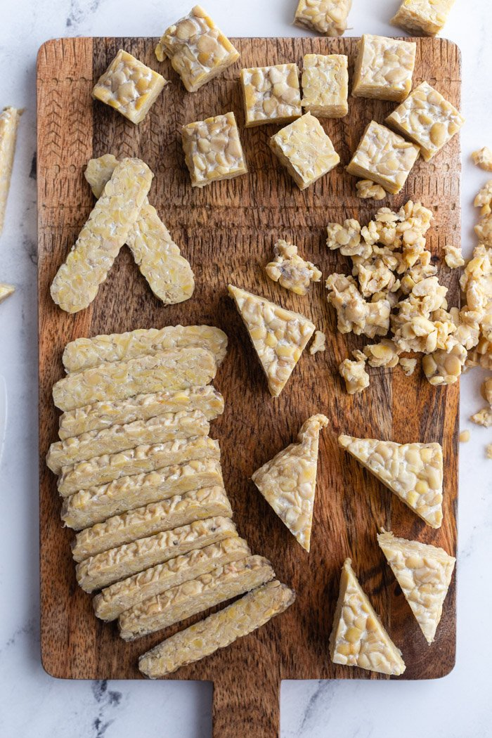 tempeh on a wood cutting board and cut into several different shapes