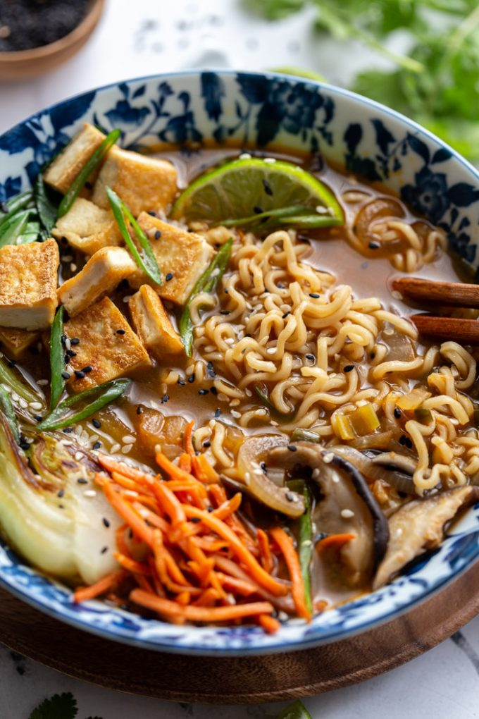 bowl filled with ramen noodles, mushrooms, carrots and bok choy