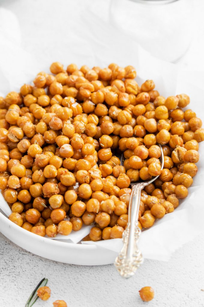 side shot of crispy chickpeas sitting in a shallow white bowl with a spoon scooping up some of the chickpeas