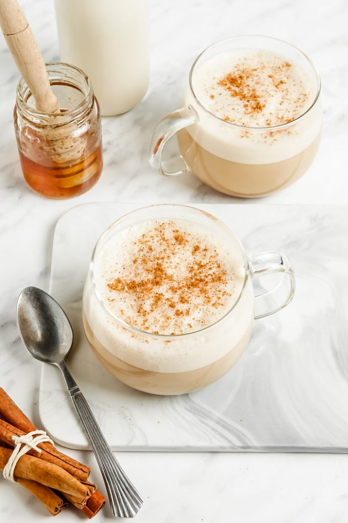oat milk lattes in a clear glass with lots of foam and cinnamon on top. Honey and milk in the background of the shot and fresh cinnamon sticks in the front