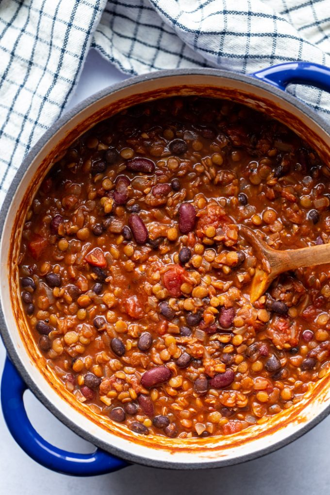 stirring lentil chili in a large pot with a wooden spoon