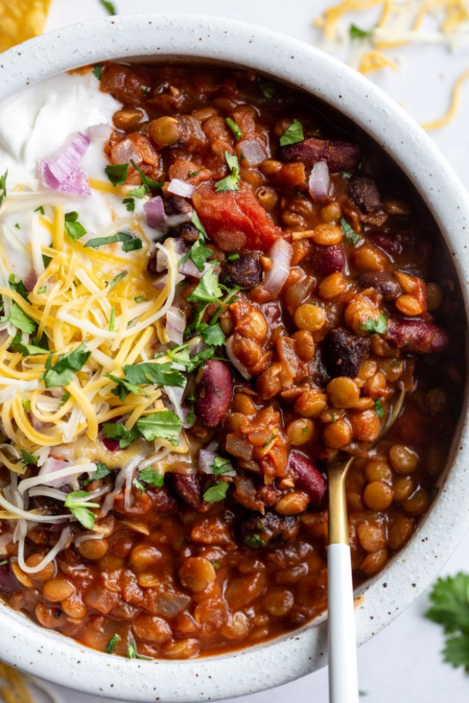 lentil chili topped with cheese, sour cream and fresh cilantro