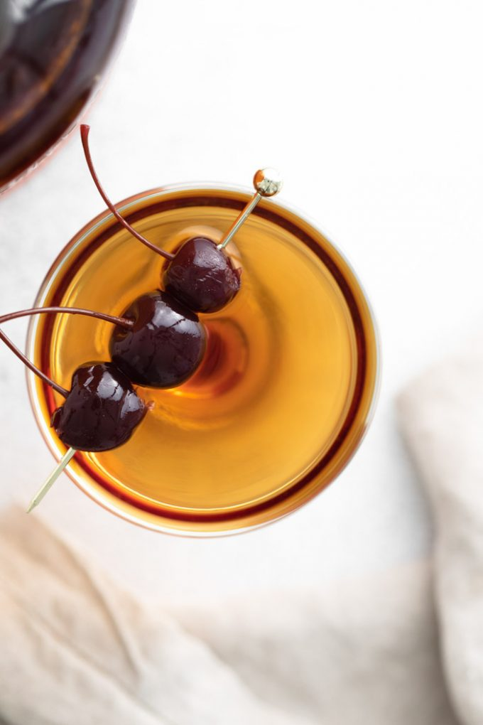 manhattan cocktail (brownish orange liquid) in a coup cocktail glass and garnished with 3 dark maraschino cherries on a gold pick