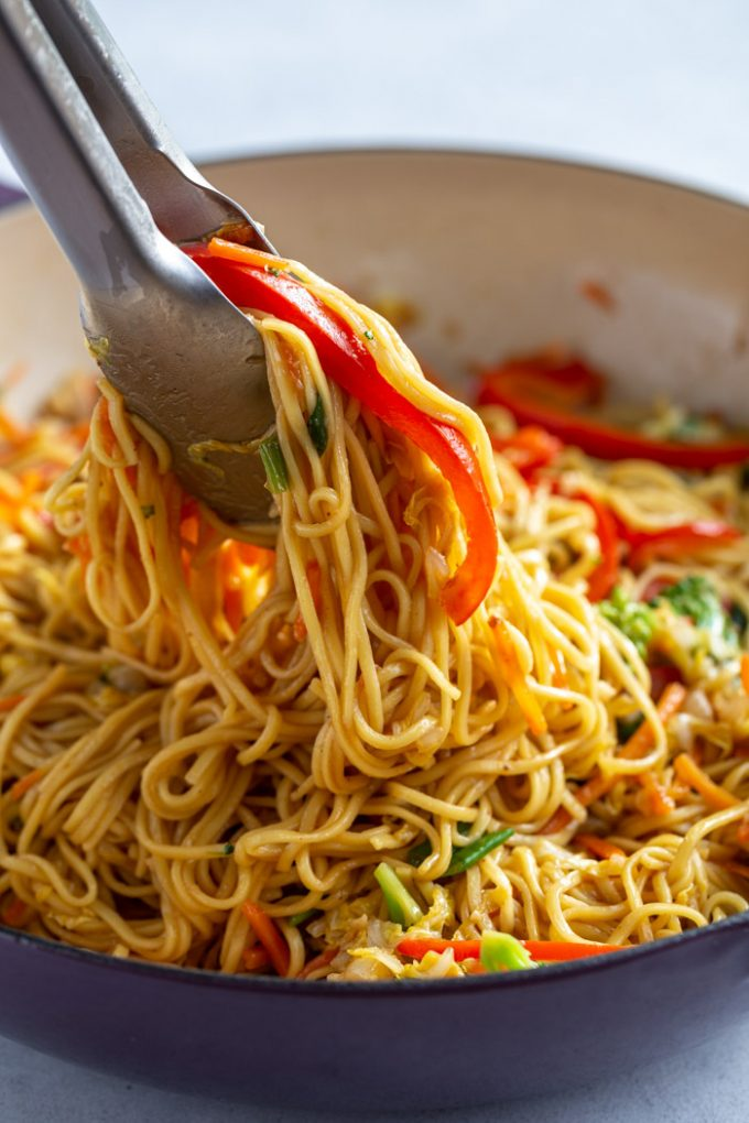 using tongs to serve Chow Mein noodles