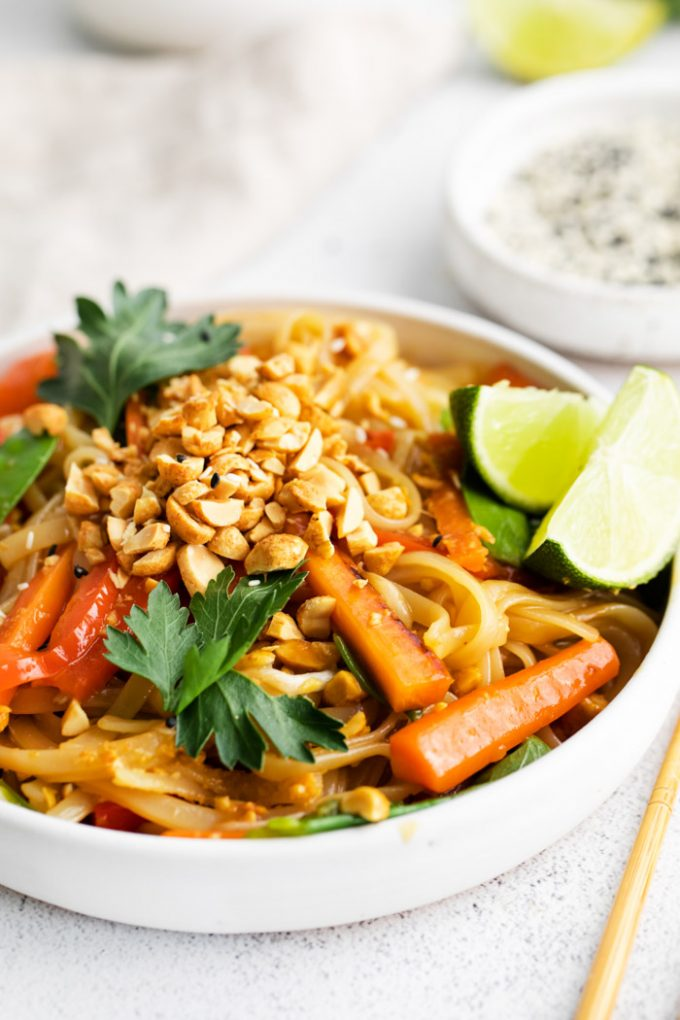 vegan Pad Thai served in a white bowl with chopped peanuts and lime wedges