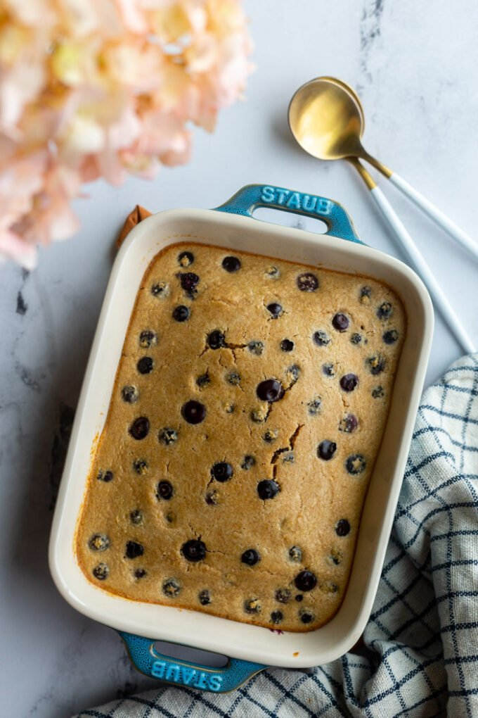 baked oats with blueberries in a small casserole dish with a napkin and spoons on the side. pink flowers in the corner of the shot