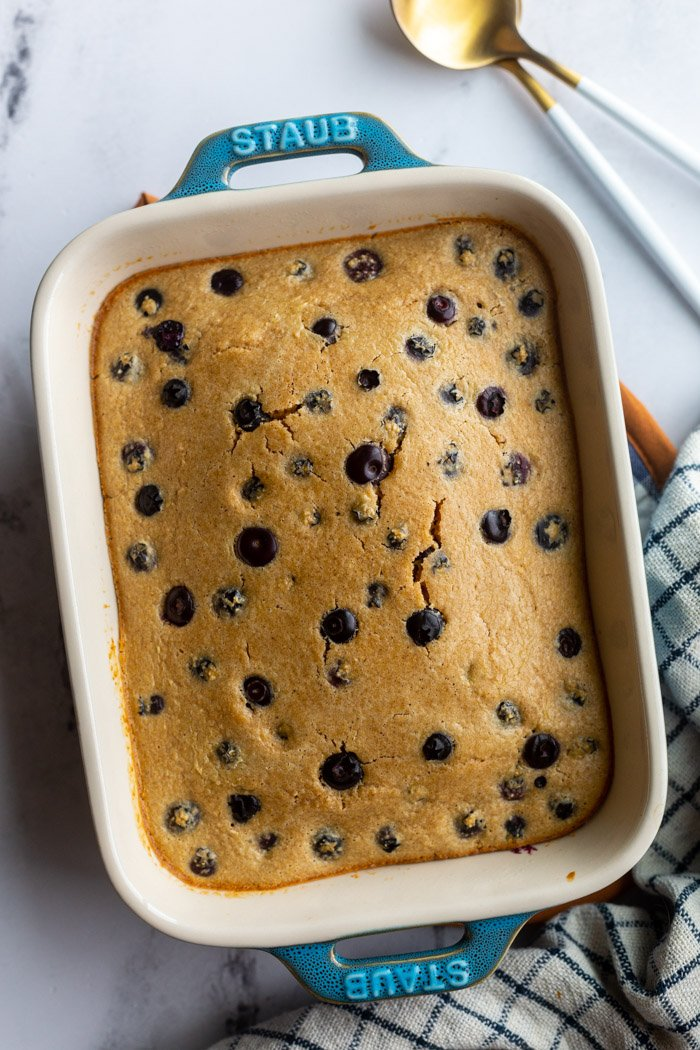 baked oats with blueberries in a small casserole dish with a napkin and spoons on the side