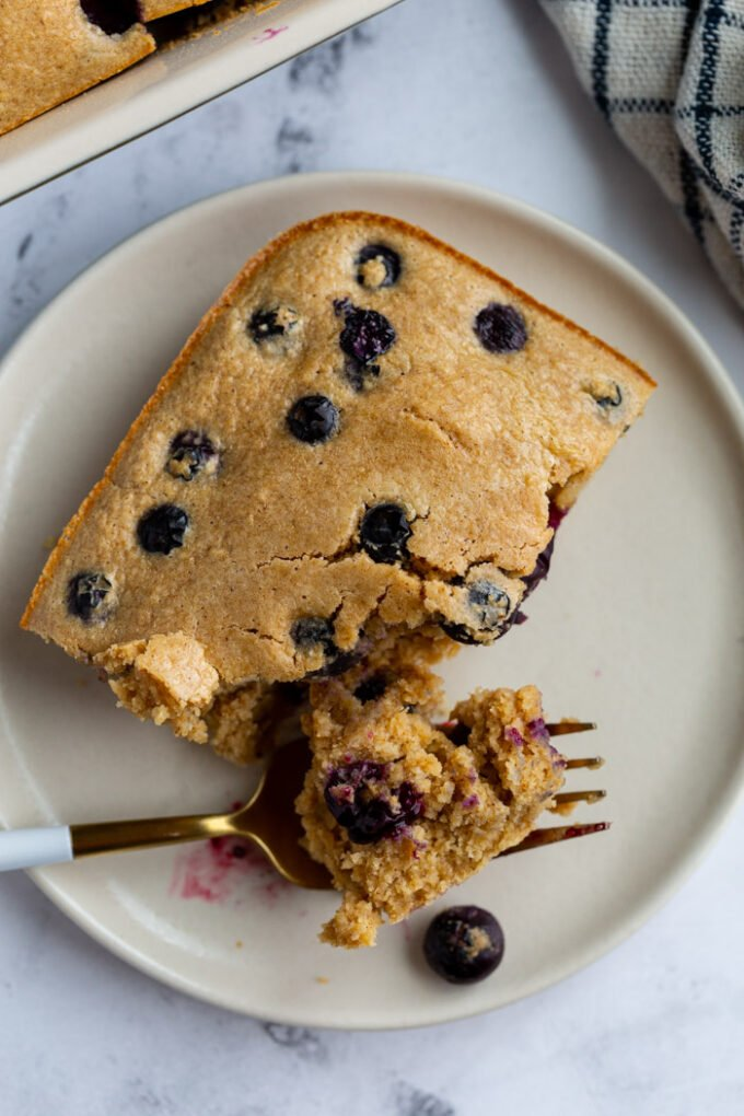 baked oatmeal on a plate with blueberries on top and a bite taken out by a fork
