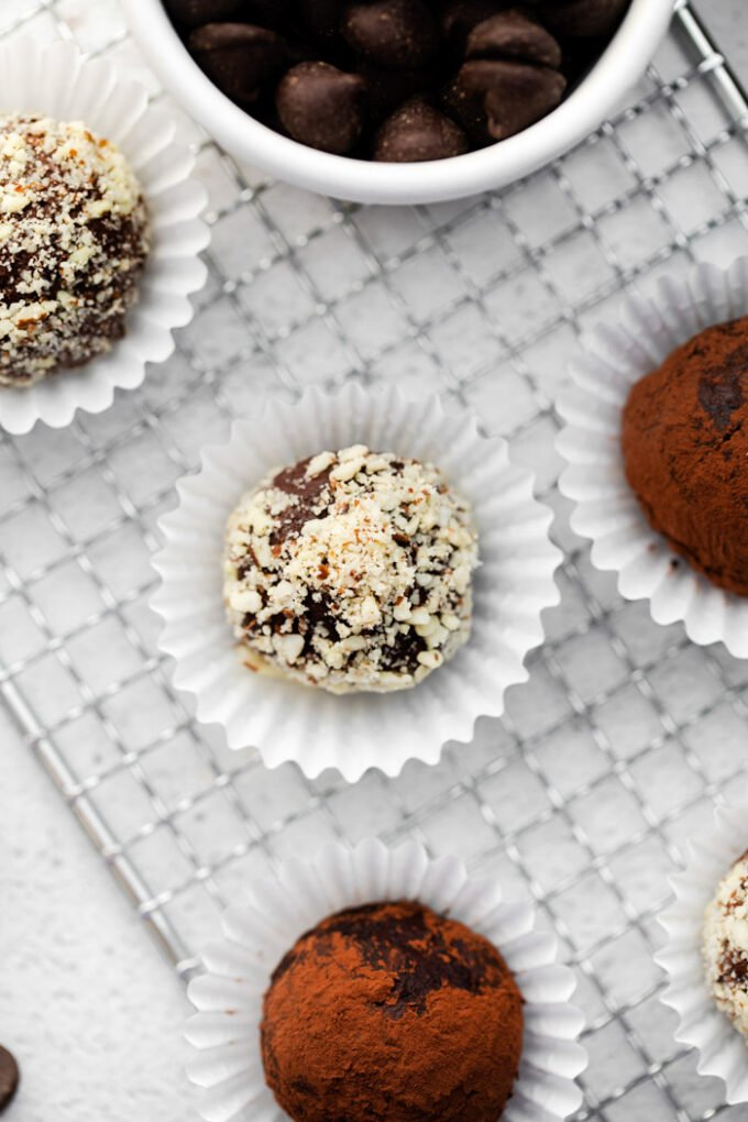 chocolate truffles covered in nuts and sitting in a mini muffin liner with more truffles around