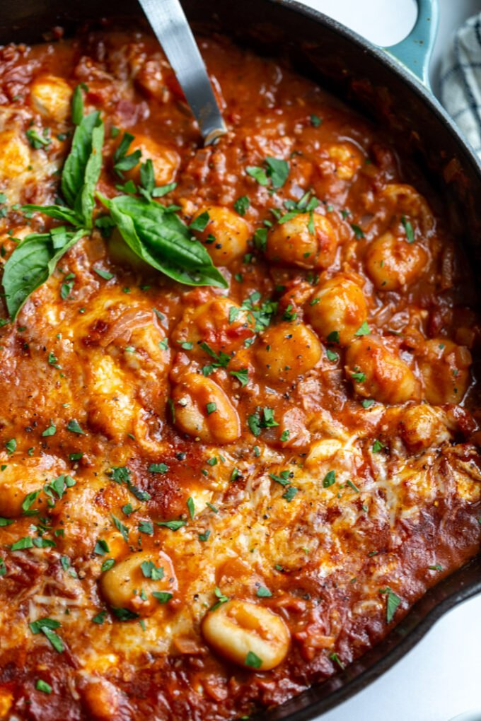 skillet with tomato sauce and gnocchi covered with cheese and garnished with fresh basil