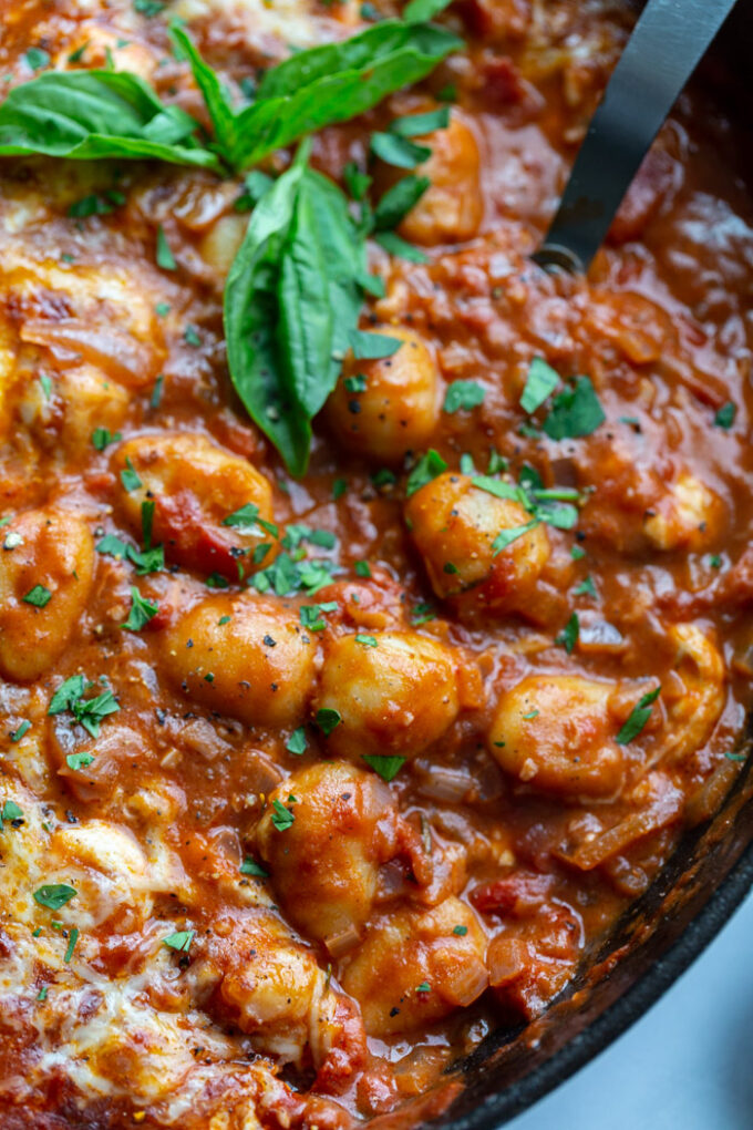 skillet with tomato sauce and gnocchi covered with cheese and garnished with fresh basil. spoon sticking out the side