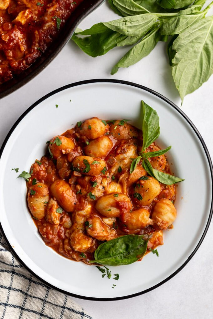 tomato sauce gnocchi in a white bowl with fresh herbs and a skillet in the corner