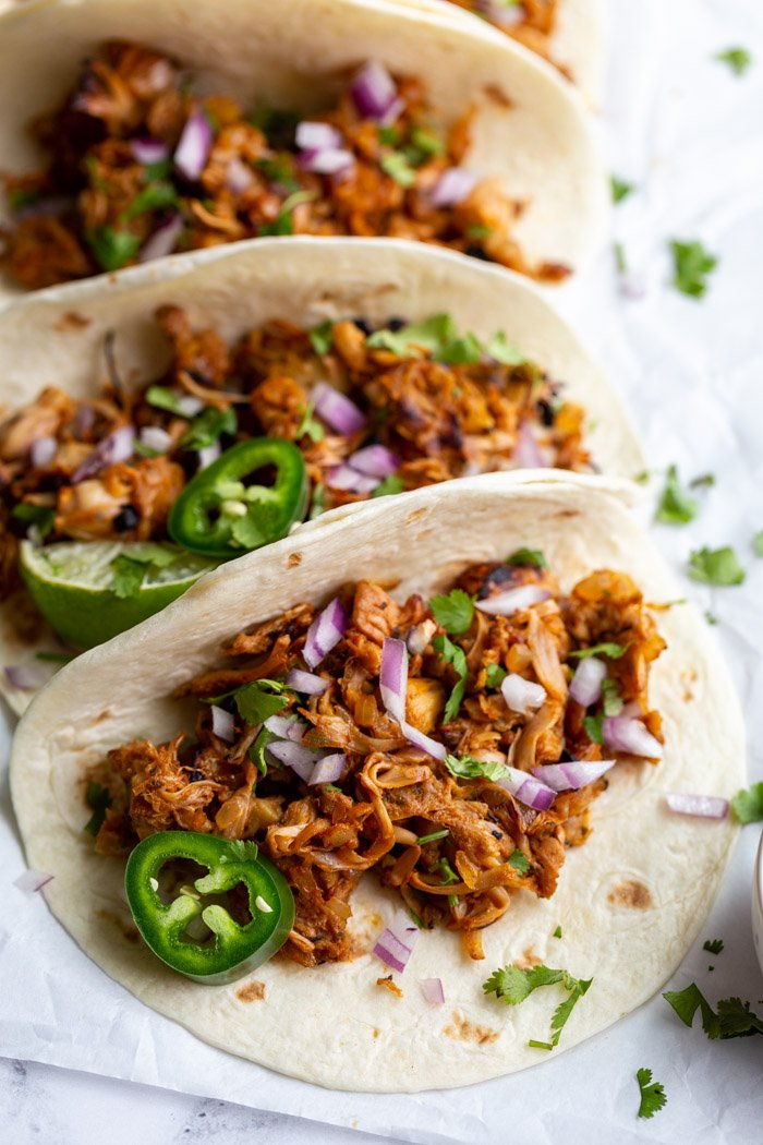 jackfruit carnitas tacos on flour tortillas and topped with onion, cilantro, and jalapeno