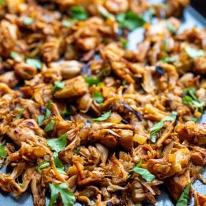 shredded jackfruit carnitas on a baking tray and topped with cilantro