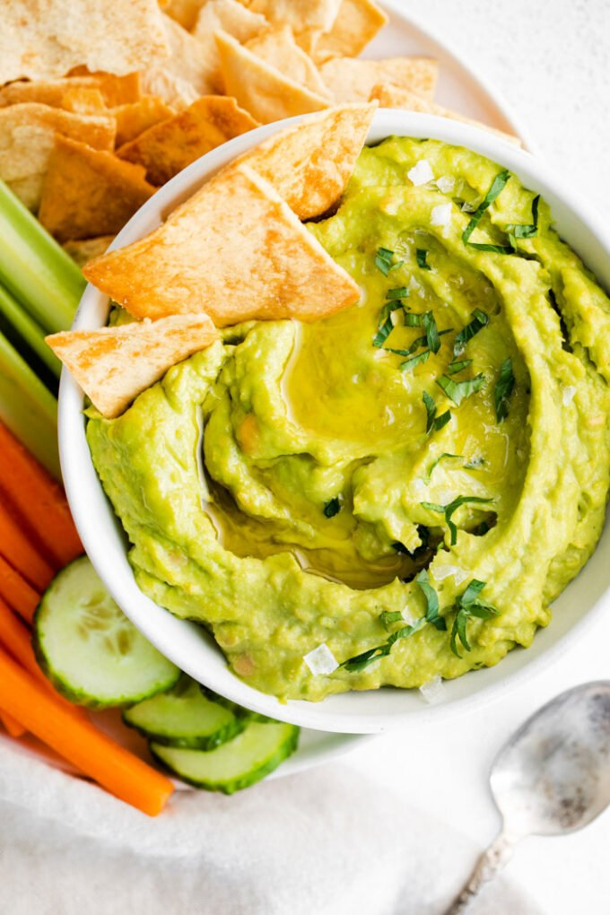white bowl filled with green avocado hummus and surrounded by chips and veggies. a few chips sticking out of the hummus