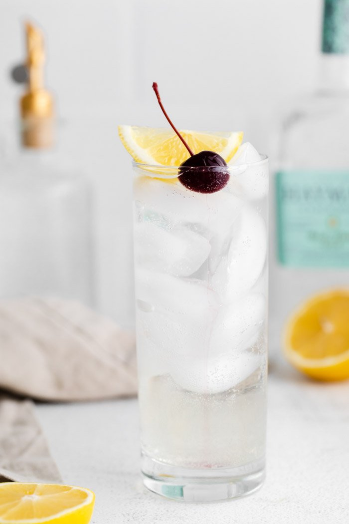 tom collins cocktail in a tall glass with ice and garnished with a lemon wedge and dark cherry. Liquor bottles in the background